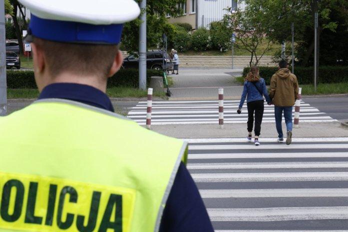 Policjant ruchu drogowego patrzy na pieszych przechodzących przez przejście.