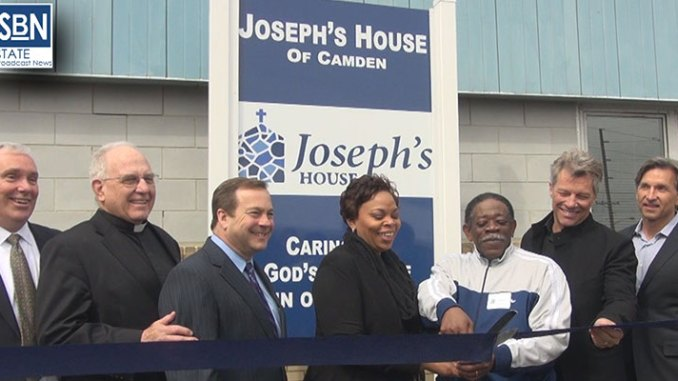 Officials watch as ribbon is cut at Joseph's House, a homeless shelter in Camden, NJ, supported by rock musician Jon Bon Jovi. From left, John Klein, executive director of Joseph's House; Msgr. Robert McDermott, pastor of St. Joseph's Pro-Cathedral, Camden; Louis Cappelli, Camden County Freeholder Director; Camden Mayor Dana Redd; Norcot Thomas, a resident of Joseph's House; Bon Jovi; and Craig Spencer, Vice Chairman of the Jon Bon Jovi Soul Foundation. Steve Lubetkin/State Broadcast News