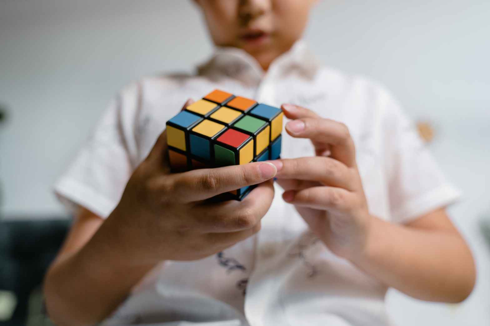 close up photo of a child solving a rubik s cube