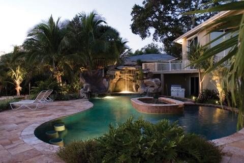 Custom Swimming Pool with Natural Stone Waterfalls and Pool Grotto pool lit up