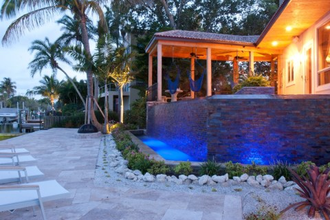 Travertine deck and modern pool with infinity edge