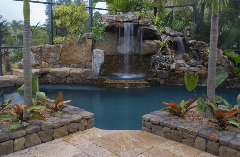 Travertine deck, stone planters and grotto waterfall