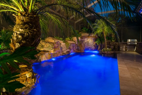 Spa, Waterwall, Grotto and OUtdoor Kitchen lit up at night