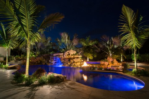 Natural lagoon pool sundeck wading area at night with fire pits and stone grotto