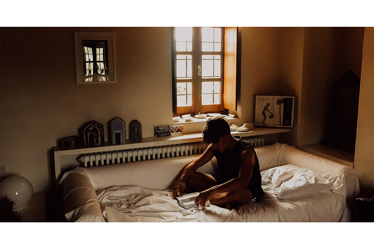 男生坐在床上看書的照片