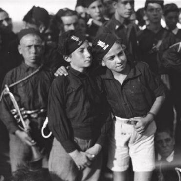 """Archivio Luce, Reparto Attualità, servizio fotografico n. 645 del 06.09.1928, """"Ritratto di due balilla, in piedi, intenti a osservare avanti, sullo sfondo del gruppo di avanguardisti"""""""