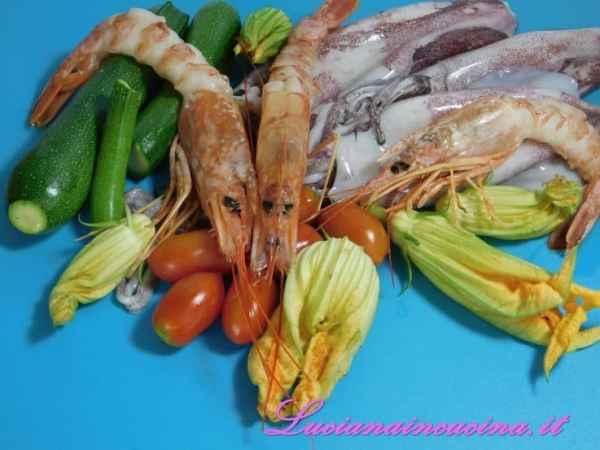 Pulire le verdure ed affettarle. Pulire poi i calamari e tagliarli a rondelle.