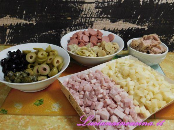 Facciamo a dadini e in piccoli pezzi tutti gli altri ingredienti:  formaggio, olive, funghetti, carciofini, tonno, ecc..