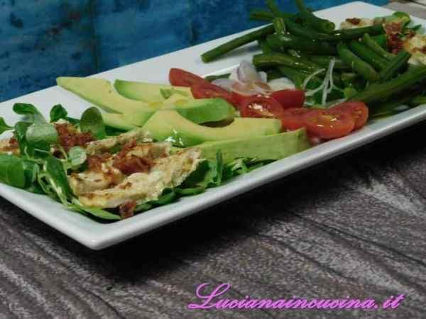 Disporre sul piatto di servizio l'insalata, i pomodorini, il cipollotto, l'avocado ed i fagiolini. Ai lati adagiare i filetti di pollo affettati e sbriciolate su di essi il bacon croccante.