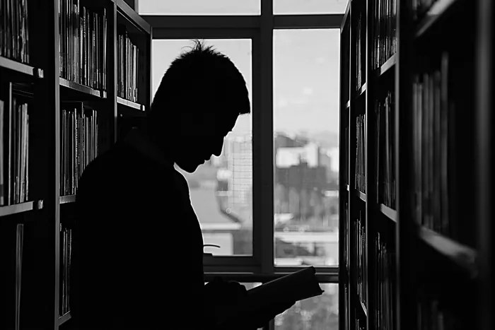 guy reading in library black and white