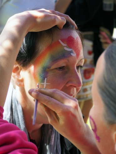 Some chick paints crosses and rainbows on herself.