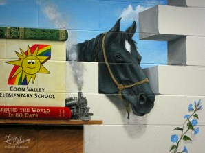Black Beauty peeks into the Library. A steam engine from Jules Vern's Around the World in 80 Days sits on the shelf with steam floating up and out toward the blue sky. Blue morning glories climb up the wall.