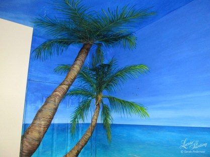 These palm trees are painted in the corner of the room, on the door and onto the ceiling, as well as on a cubic box that extends into the room. Tropical birds fly in the distance over the ocean.