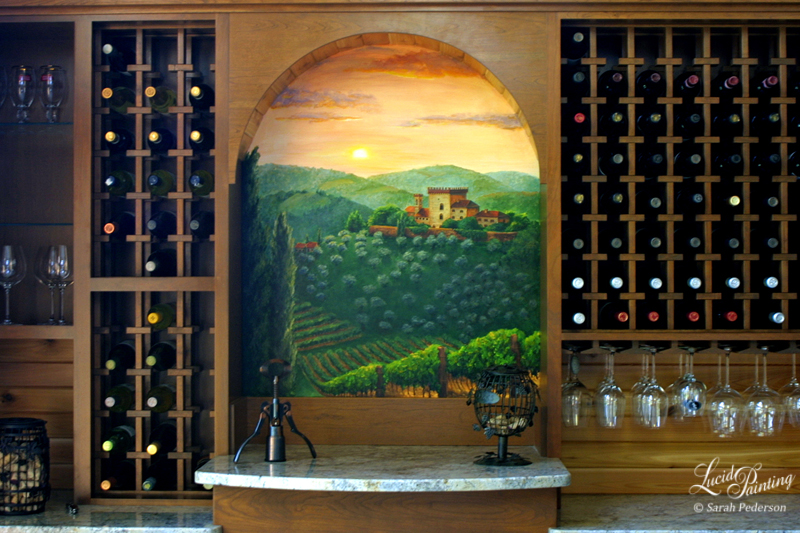 This existing recessed wall between wine racks with an arched wood border was built to include a mural that would remind my clients of their vacations to Italy. The landscape features a castle nestled in the distant hills with an olive grove in the middle and a vineyard in the foreground. The setting sun adds a warm glow to the entire scene with muted oranges and violets that coordinate with a nearby wall.