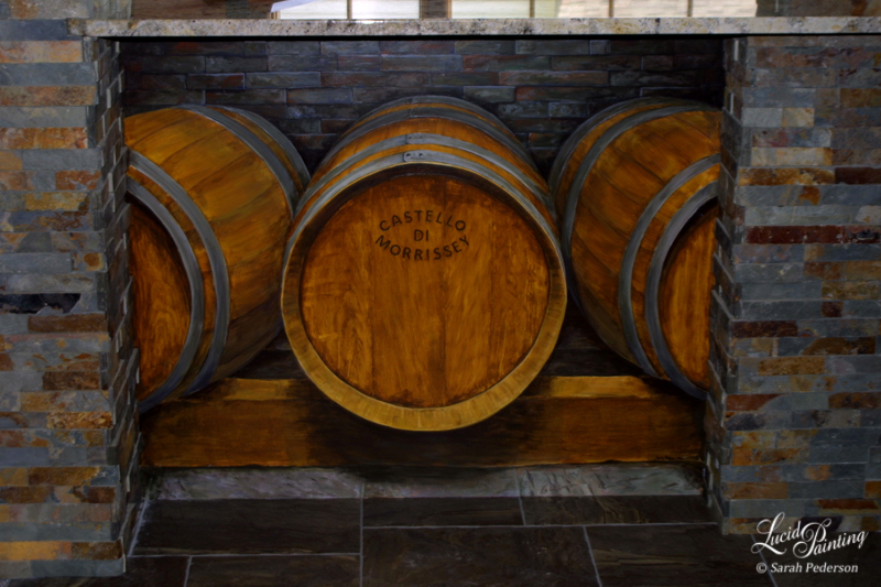 Three life-sized wine barrels are painted in perspective on a flat wall under a countertop in a residential home. The middle barrel features my client's name, and appears to be branded into the wood.