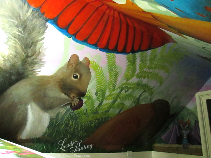 This large fluffy squirrel is eating a colorful mushroom and sitting under a large mushroom. A fern is behind him and behind the over-sized acorn.