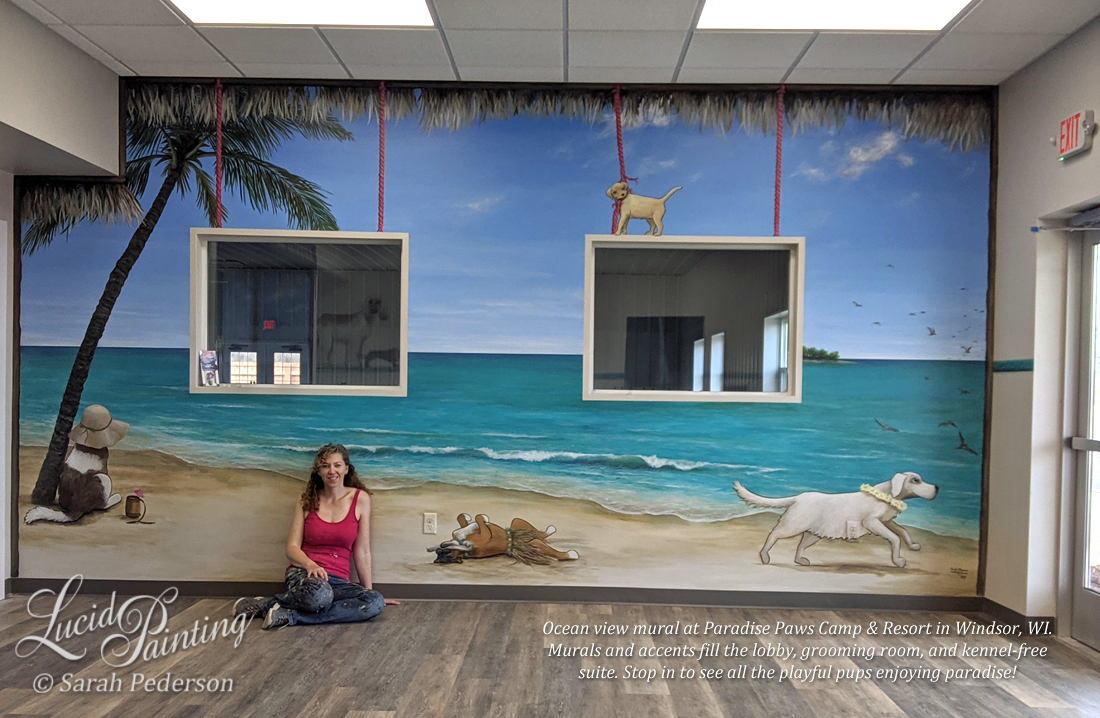 "Artist Sarah Pederson sits in front of a mural showing an ocean view with turquoise  water and blue skies. Cartoon dogs relax on the beach. A Saint Bernard stares out at the view, a boxer lies on his back chewing a bone, a golden retriever chases shore birds, and a Labrador Retriever chews on a support that holds the ""window"" in place. Thatch from a tiki hut appears to hang down from the ceiling."