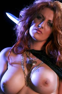 Drakaina bares her beautiful breasts while weilding a sword.