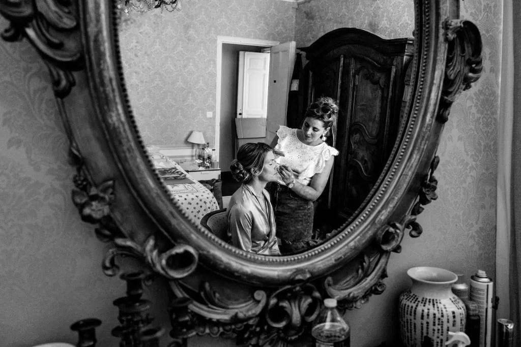 photo préparatif maquillage de la mariée dans un miroir en noir et blanc
