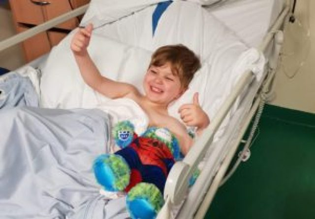 Gregory with big grin giving a double thumbs up from a hospital bed
