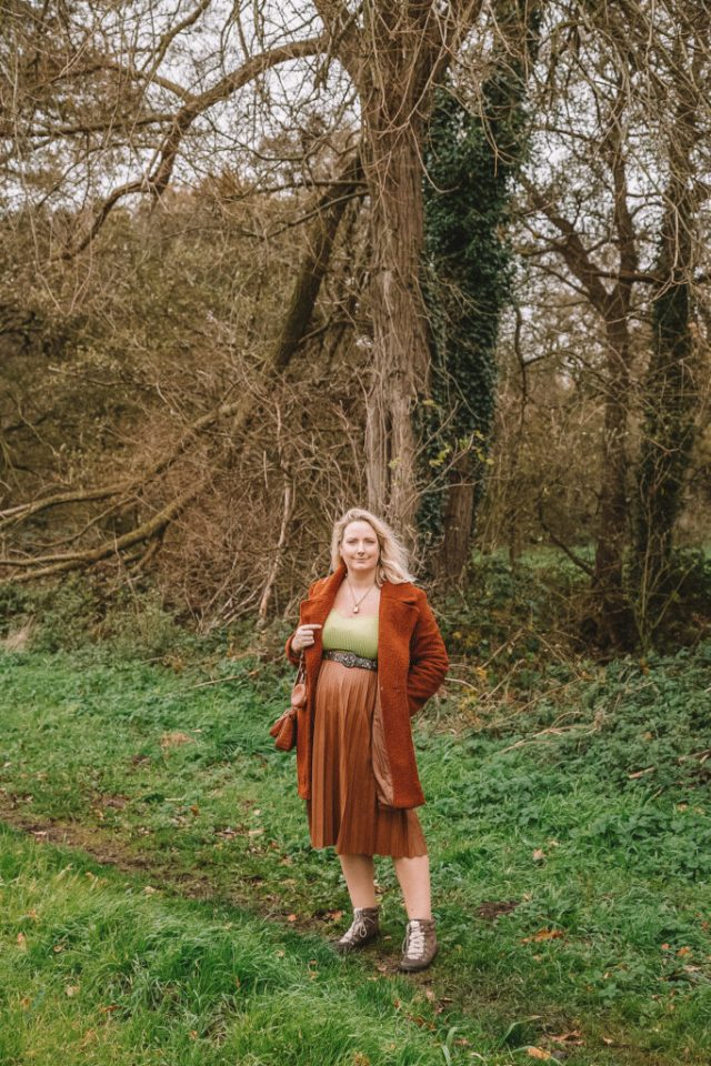 Lucy stood in a field with trees behind and wearing a pleather skirt, lime green knitted top and boots