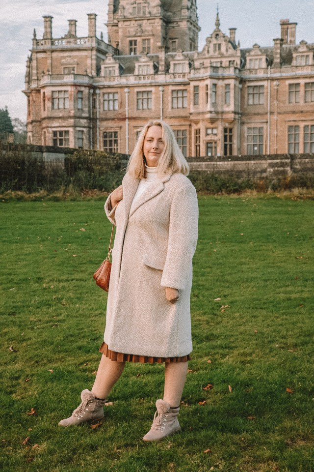 Lucy in front of a hall in a neutral outfit of coat and boots