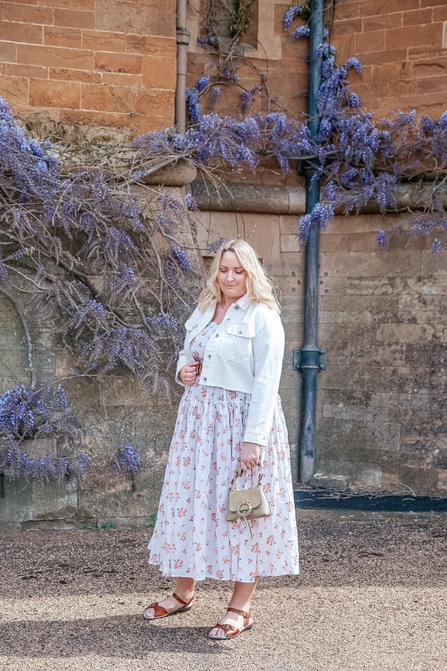 lucy is wearing a floral dress and crop denim jacekt and is stood in front of some wisteria