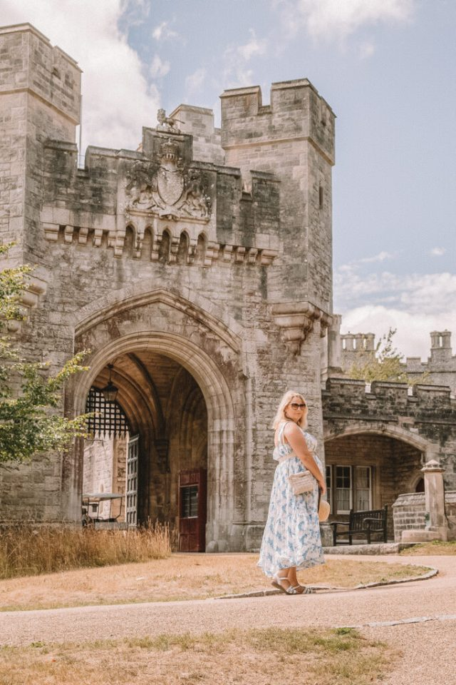 lucy is stood in front of a castle gate in a blue and white lrona luxe x in the style maxi dress