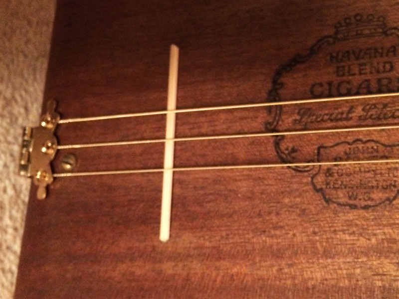 A matchstick holds the strings proud of the box.