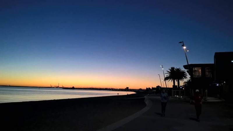 Lungomare al tramonto con due runner