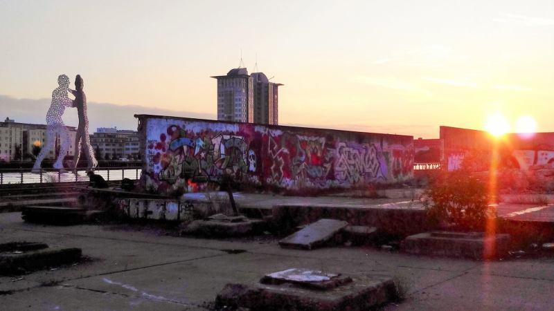 Berlino al tramonto con un pezzo di muro e scultura sul fiume