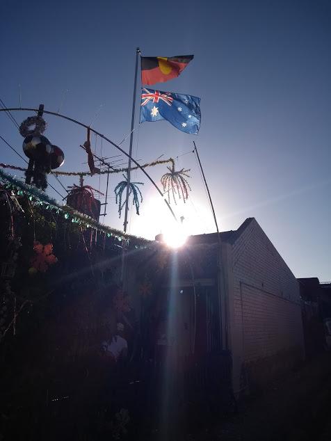sole dietro a bandiera australiana e aborigena