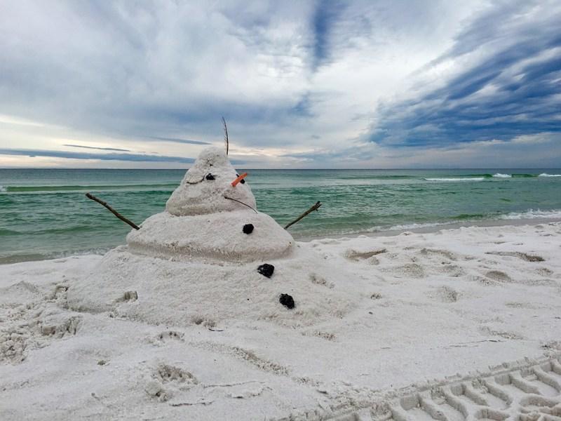 pupazzo di neve fatto di sabbia in spiaggia