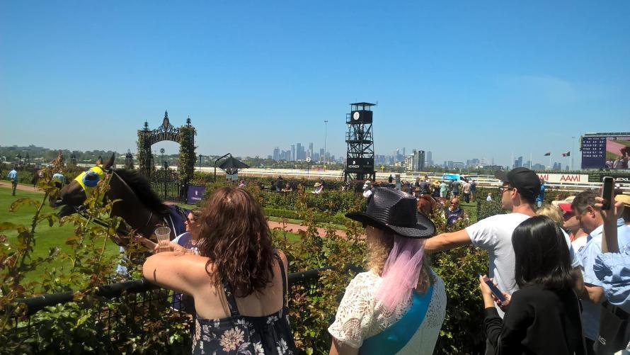 spettatori di spalle che guardano le corse dei cavalli al flemington racehorse di melbourne con skyline sullo sfondo