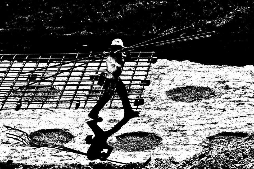 Steel worker carrying steel rods in construction site
