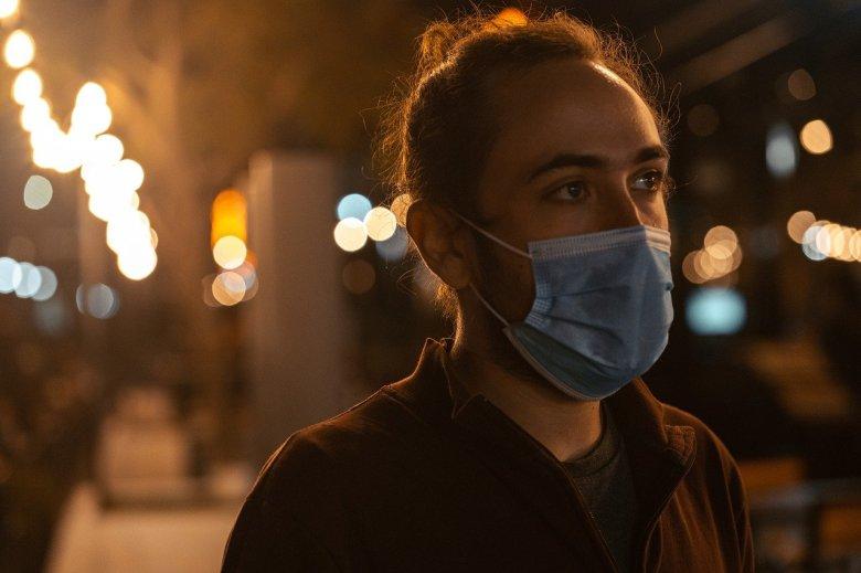 Junger Mann mit OP-Maske im Gesicht