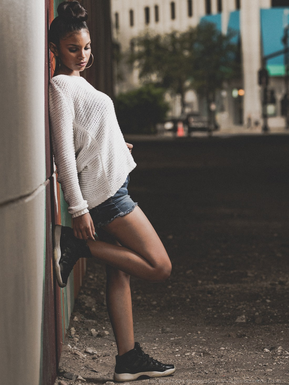 urban photography young woman reclines against a wall in a modern way luis betancourt photography