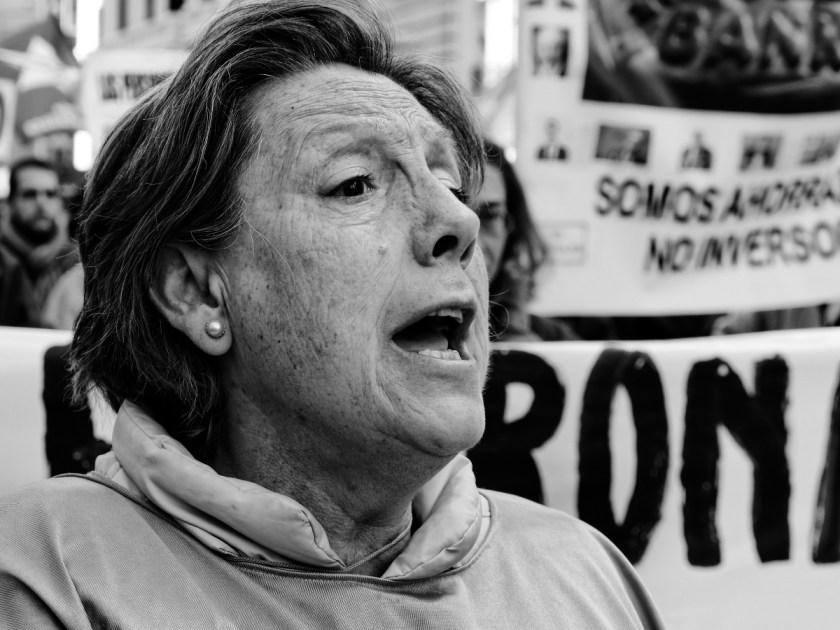 Mujer mayor gritando en manifestación con pancarta de fondo. Manifestación en Madrid contra los recortes del Partido Popular y el desmantelamiento del Estado de Bienestar en España. Fotografía de Luis F. Roncero.
