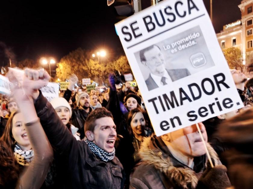 """Joven gritando y pancarta con la foto de Mariano Rajoy: """"SE BUSCA: TIMADOR EN SERIE"""" Rodea el Congreso: manifestación en Madrid contra la Ley Mordaza del Partido Popular. Fotografía de Luis F. Roncero."""