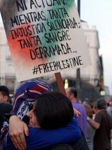 Mujeres se abrazan en una manifestación. Sostienen una pancarta contra los crímenes de Israel. Manifestación contra el genocidio de Israel en Gaza.. By Luis F. Roncero
