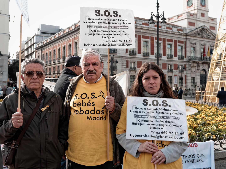 Tres manifestantes con pancartas en la Puerta del Sol protestan por el caso de los bebés robados en las maternidades de Madrid. Fotografía de Luis F. Roncero.
