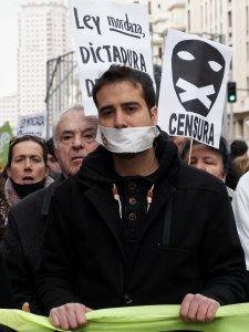 Manifestante amordazado con pancartas contra la censura y la dictadura. Manifestación contra la Ley Mordaza en Madrid. By Luis F. Roncero