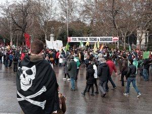 """Chico envuelto en bandera pirata observa pancarta """"Pan, trabajo, techo y dignidad"""". Marchas de la Dignidad. Manifestación en Madrid. By Luis F. Roncero"""