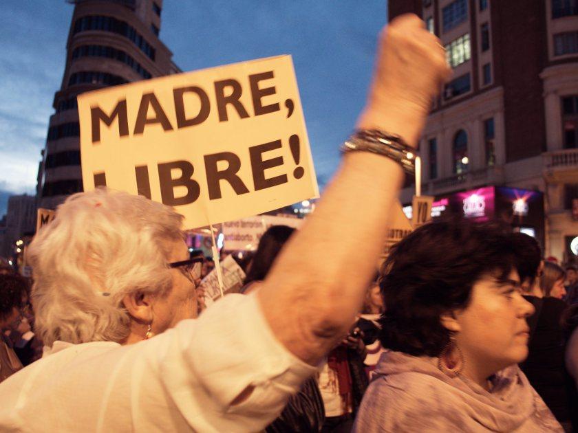 """Mujer manifestándose con el puño en alto y una pancarta de """"Madre Libre"""". Manifestación en Madrid contra la reforma de la ley del aborto del Partido Popular. Fotografía de Luis F. Roncero."""