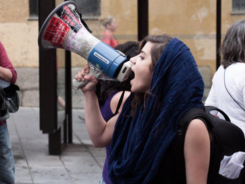 Chica joven gritando con megáfono y pañuelo violeta en la cabeza. Manifestación en Madrid contra la reforma de la ley del aborto del Partido Popular. Fotografía de Luis F. Roncero.