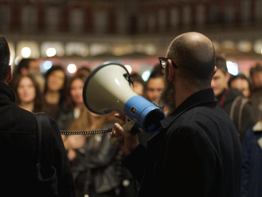 Carlos Arévalo, de La Felguera Editores, con un megáfono en la Plaza Mayor de Madrid. Fotógrafo: Luis F. Roncero.