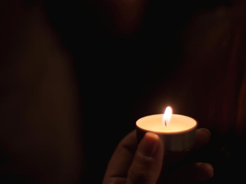 Dedos sujetando vela en la oscuridad. Fotógrafo: Luis F. Roncero.