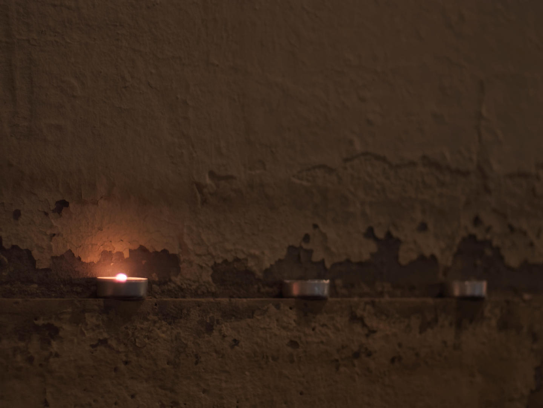 Ofrenda de velas en la repisa de una pared. Fotógrafo: Luis F. Roncero.