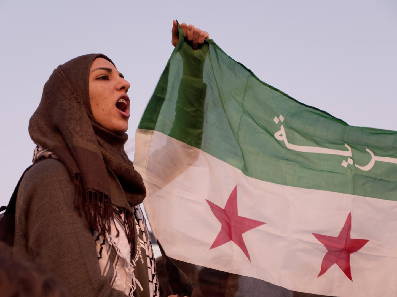 Mujer musulmana sistiene una bandera siria con el puño en alto. Concentración por los derechos de los refugiados en la Puerta del Sol de Madrid. Fotografía de Luis F. Roncero.