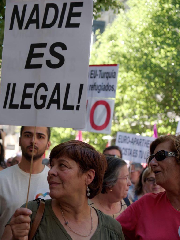 """Mujer con pancarta """"NADIE ES ILEGAL"""". Manifestación en Madrid celebrando el Día Mundial del Refugiado. Fotografía de Luis F. Roncero."""